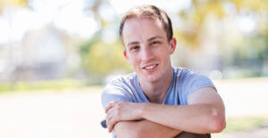Man in grey shirt smiling with arms crossed