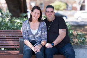 couple smiling on park bench