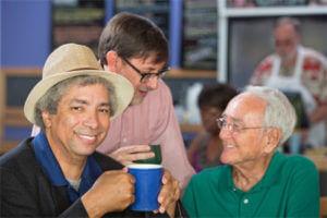 Two men drinking coffee smiling